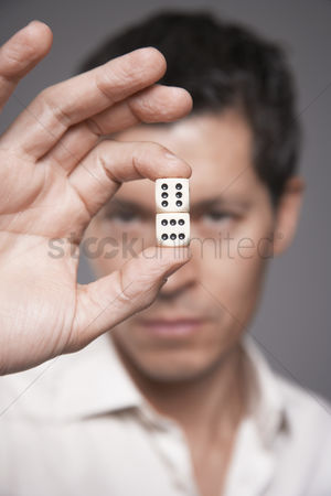 Magic : Man holding dice between finger and thumb focus on foreground