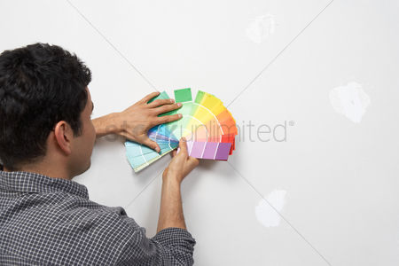 Arts : Man holding paint colour samples against interior wall back view
