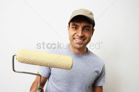 Interior : Man holding paint roller portrait