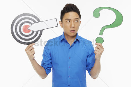 Masculinity : Man holding up a dart board along with a question mark symbol