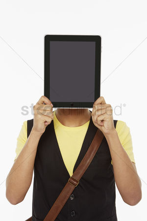 Portability : Man holding up a digital tablet  covering his face