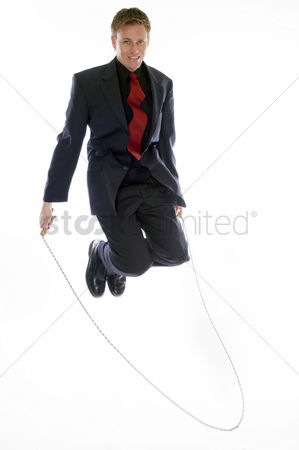 Alert : Man in business suit playing with skipping rope