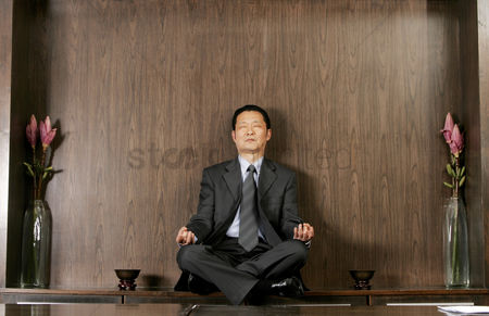 Thought : Man in business suit sitting on the shelf meditating