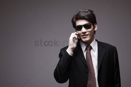 Man suit fashion : Man in full suit with sunglasses talking on the phone
