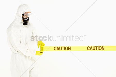 Masculinity : Man in protective suit rolling out the  caution  tape