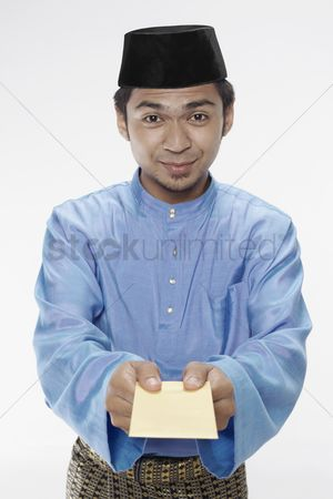 Baju melayu : Man in traditional clothing giving blank packet