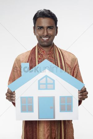 Traditional clothing : Man in traditional clothing holding a cutout house