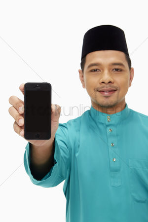 Traditional clothing : Man in traditional clothing holding up a mobile phone