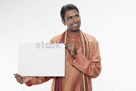 Traditional clothing : Man in traditional clothing holding up blank placard