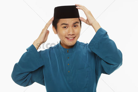 Baju melayu : Man in traditional clothing putting on his skull cap