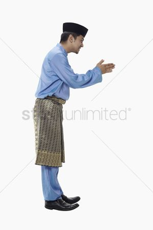 Baju melayu : Man in traditional clothing showing greeting gesture