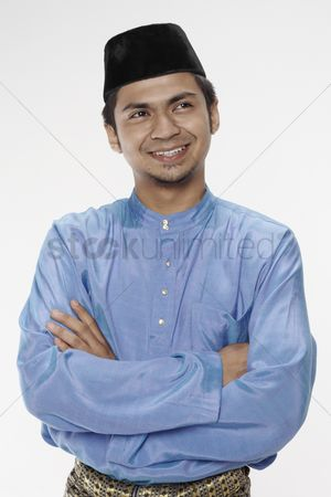 Baju melayu : Man in traditional clothing standing with arms across his chest