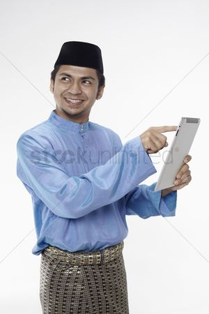 Traditional clothing : Man in traditional clothing using digital tablet