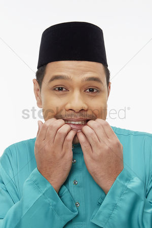 Baju melayu : Man in traditional clothing with a fearful facial expression