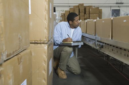 Notepad : Man inspecting boxes on conveyor belt in distribution warehouse