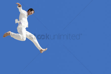 Black background : Man jumping mid air low angle view