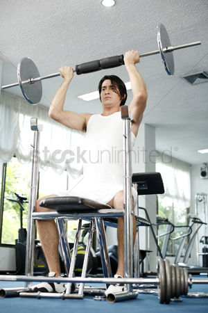 Strong : Man lifting barbell in the gym