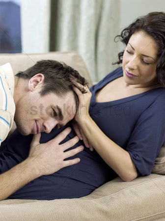 Husband : Man listening to his pregnant wife  stomach