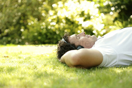 Relaxing : Man listening to music on the headphones while lying on the field