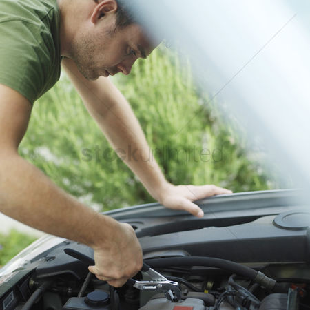 Fixing : Man looking under car hood  fixing car with pliers