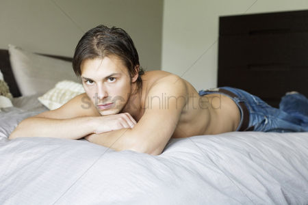 Lying forward : Man lying forward on the bed staring at the camera