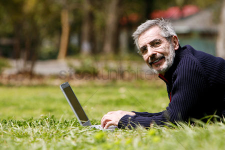 Bespectacled : Man lying forward on the grass using laptop