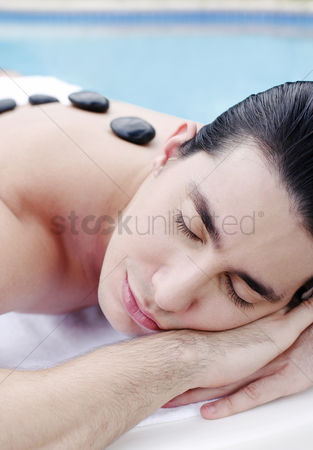 Lying forward : Man lying forward with therapeutic hot stones on his back