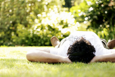 Outdoor : Man lying on the grass listening to music on the headphones