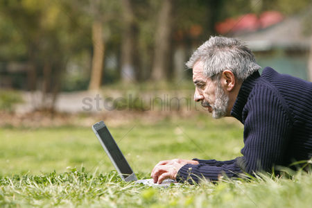 Lying forward : Man lying on the grass using laptop