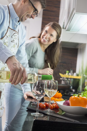 Wine bottle : Man pouring white wine in glasses while cooking with woman at kitchen