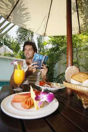 Sausage : Man reading book with breakfast on the table