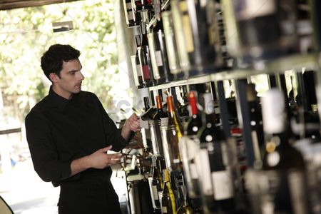 Refreshment : Man selecting wine bottle from rack