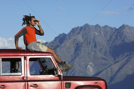 Day off : Man shading eyes on top of jeep near mountains
