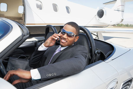 Smiling : Man sitting in convertible near private jet talking on mobile