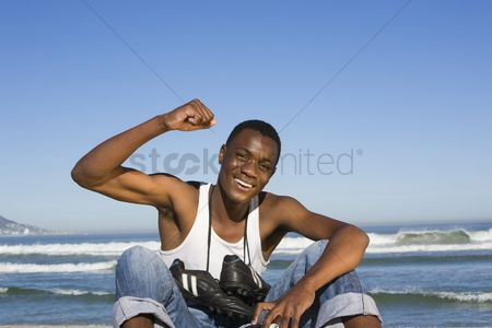 Arm raised : Man sitting on beach with with football boots round his neck cheering
