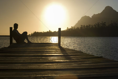 Mid adult man : Man sitting on dock by lake side view