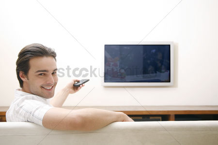 Resting : Man sitting on the couch holding a television remote control