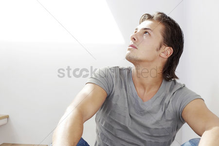 Alert : Man sitting on the staircase looking up