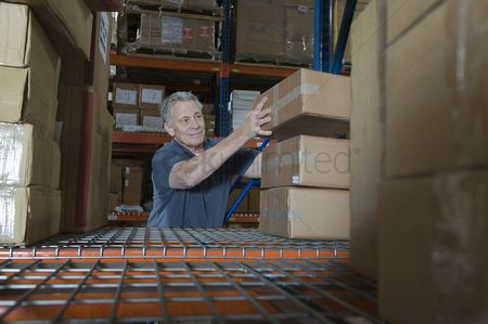 Interior : Man stacking boxes in distribution warehouse