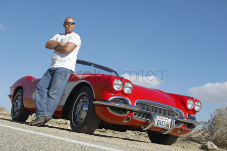Car : Man standing beside classic car on road