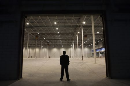 Spacious : Man stands with hands in pockets at warehouse entrance
