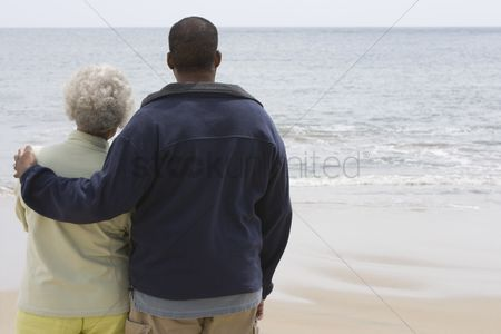 Jacket : Man stands with his arm round a woman at waters edge