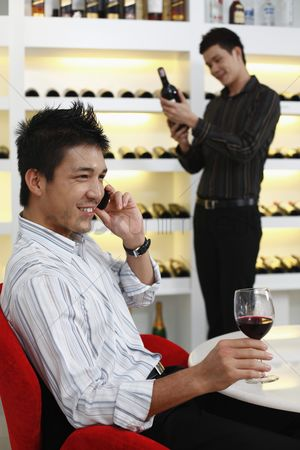 Choosing : Man talking on the phone  another man is choosing wine in the background