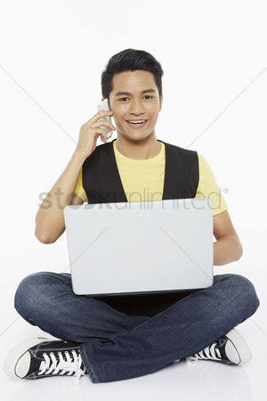 Portability : Man talking on the phone while using laptop