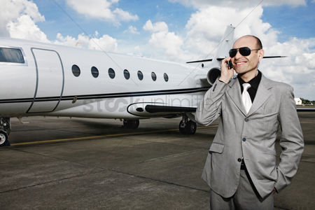 Pocket : Man talking on the phone with private jet in the background
