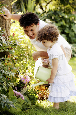 Closeness : Man watching his daughter watering plants
