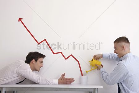Eastern european ethnicity : Man watering pot of line graph encouraging business growth  another man watching