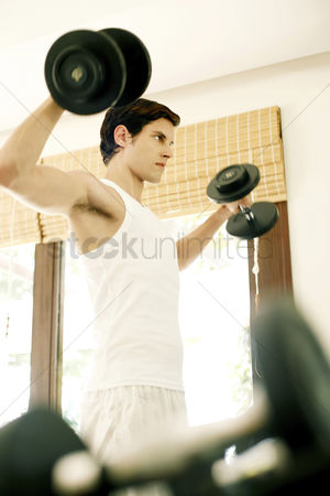 Dumbbell : Man weight lifting in the gymnasium