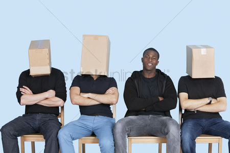 Blue background : Man with friends faces covered with cardboard boxes as they sit on chairs over blue background