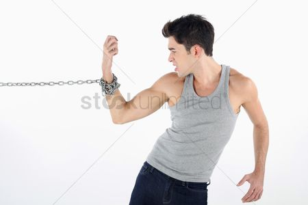 Frowning : Man with hand tied to a chain  pulling hard